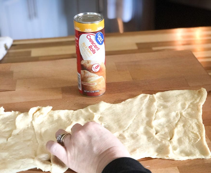 pressing seams of crescent dough together to form one sheet of dough