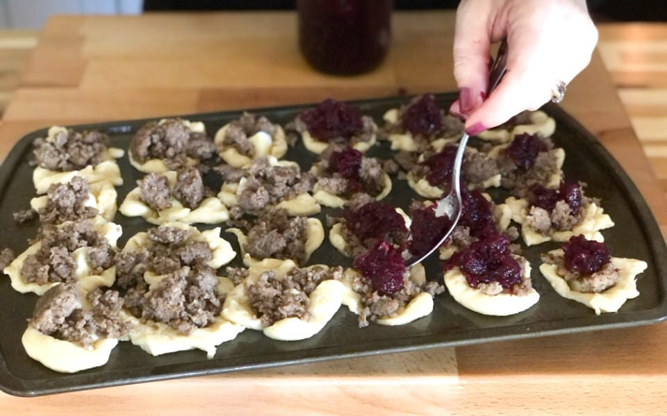 spooning a touch of cranberry on top of sausage brie bites