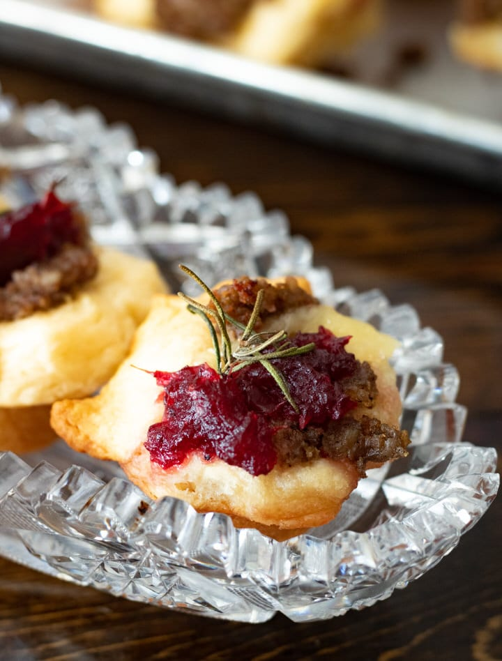 close up of sausage brie bites with cranberry in a crystal dish