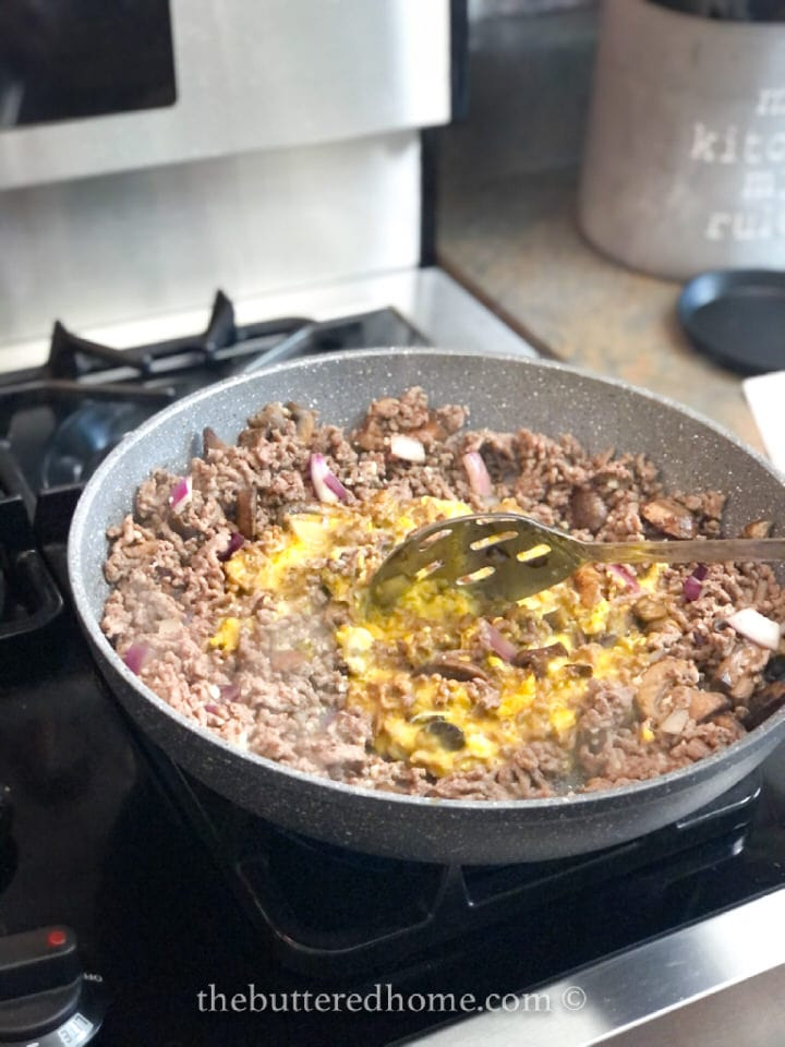 pulling the cooked meat into the eggs